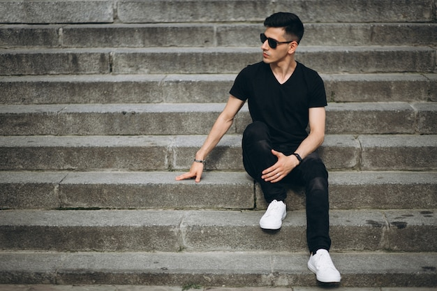 Joven guapo sentado en las escaleras