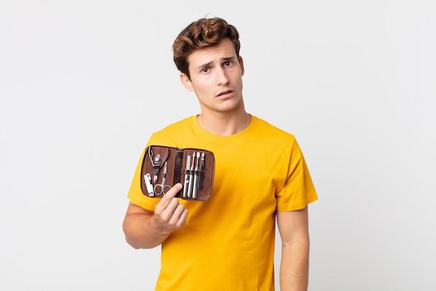 Joven guapo sintiéndose desconcertado y confundido y sosteniendo una caja de herramientas de uñas