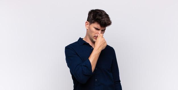 Joven guapo sintiéndose disgustado, tapándose la nariz para evitar oler un hedor desagradable y desagradable