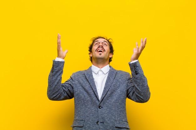 Joven guapo sintiéndose feliz, asombrado, afortunado y sorprendido, celebrando la victoria con ambas manos en el aire contra la pared naranja