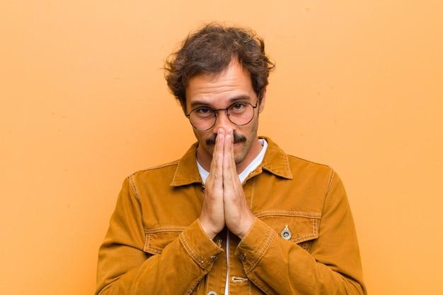 Joven guapo sintiéndose preocupado, esperanzado y religioso, rezando fielmente con las palmas presionadas, pidiendo perdón contra la pared naranja