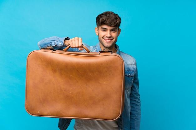 Joven guapo sobre azul aislado sosteniendo un maletín vintage