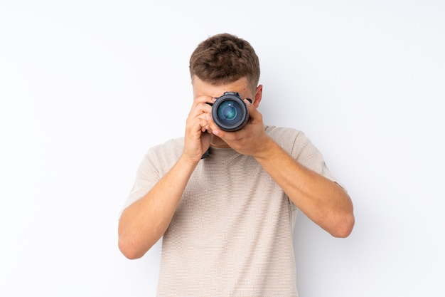 Joven guapo sobre blanco con una cámara profesional