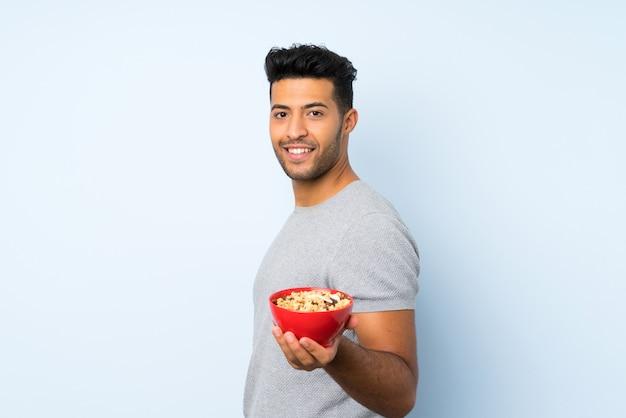 Joven guapo sobre fondo aislado sosteniendo un tazón de cereales