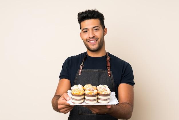 Joven guapo sobre pared aislada con mini tortas