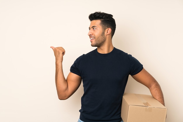 Joven guapo sobre pared aislada sosteniendo una caja para moverla a otro sitio y apuntando hacia el lado