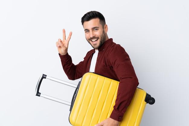 Joven guapo sobre pared blanca aislada en vacaciones con maleta de viaje y haciendo gesto de victoria