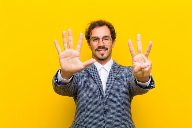 Joven guapo sonriendo y mirando amigable, mostrando el número ocho u octavo con la mano hacia adelante, contando contra naranja