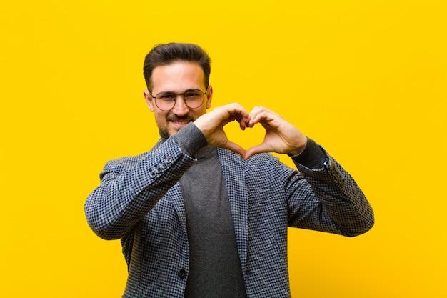 Joven guapo sonriendo y sintiéndose feliz, lindo, romántico y enamorado, haciendo forma de corazón con ambas manos contra la pared naranja