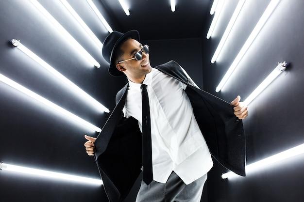 Joven guapo sonriente hipster negro en traje de estilo retro vintage bailando hip hop en discoteca discoteca, divirtiéndose