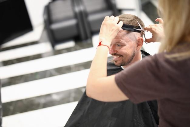 Joven guapo sonriente sentado en la silla de peluquería y haciendo retrato de lavado