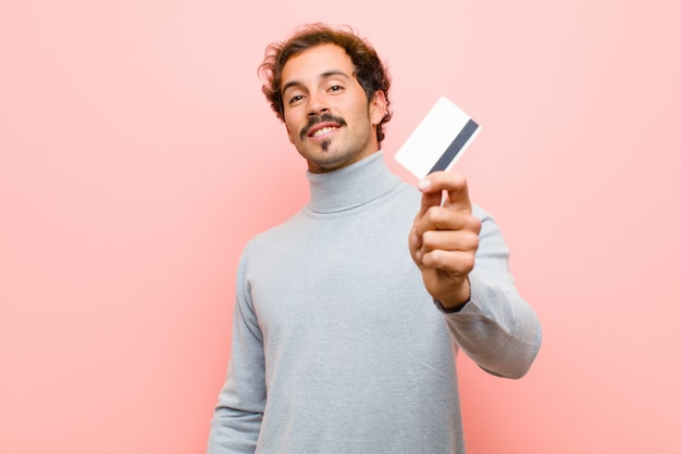 Joven guapo con una tarjeta de crédito contra rosa plana