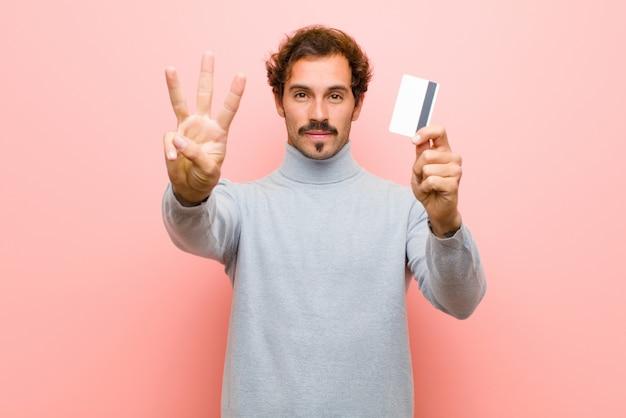 Joven guapo con una tarjeta de crédito rosa pared plana