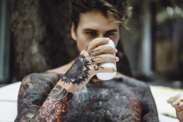 Joven guapo tatuado desayunando en la cama al aire libre al aire libre en el jardín