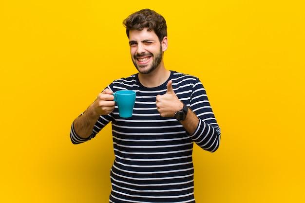 Joven guapo tomando un café contra la pared naranja