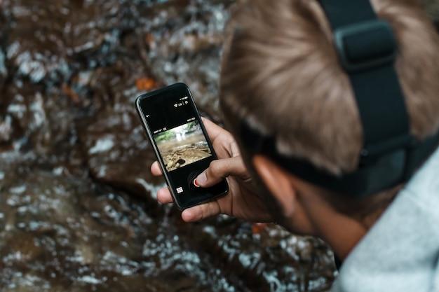 Joven guapo tomando foto de cascada cerca