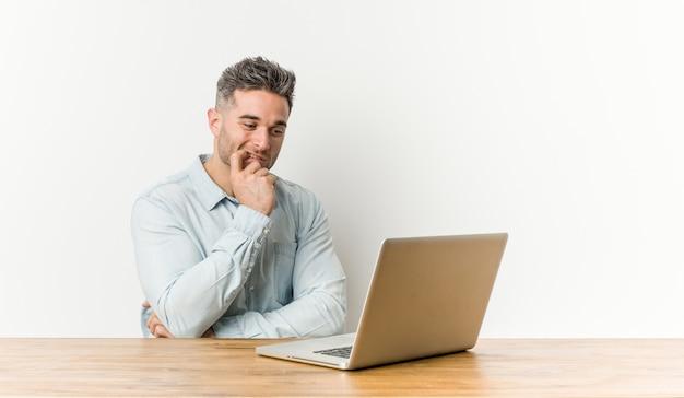 Joven guapo trabajando con su computadora portátil relajado pensando en algo