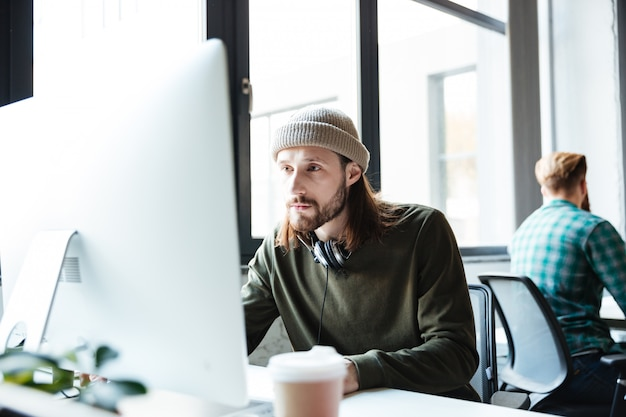 Joven guapo trabajar en oficina usando computadora
