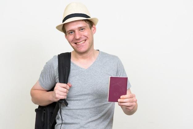 Joven guapo turista escandinavo contra la pared blanca.