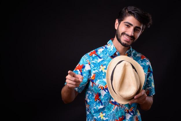 Joven guapo turista persa barbudo listo para vacaciones en negro