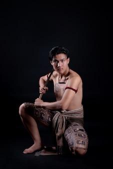 Joven guerrero masculino de tailandia posando en una posición de combate con una espada