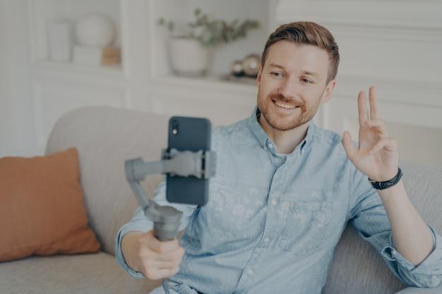 Joven hablando con su amigo a través del chat de video en línea usando el teléfono conectado al cardán, saludando con la mano mientras sonríe, feliz después de no verse durante mucho tiempo