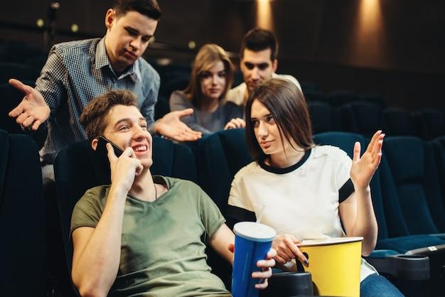 Joven hablando por teléfono en el cine, audiencia insatisfecha. showtime, ver películas