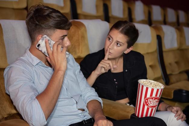 Joven hablando por teléfono móvil durante ver película.