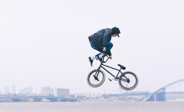 Un joven hace un truco de tailwhip en el aire en una bicicleta bmx.