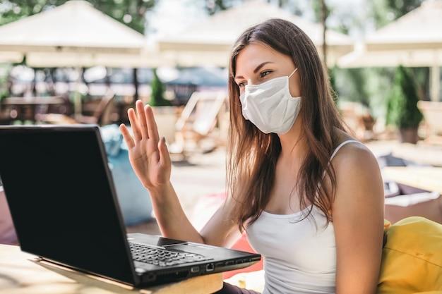 Una joven hace una videoconferencia y se sienta en la playa con una máscara protectora. mujer independiente con mascarilla médica sentado con portátil y hablando