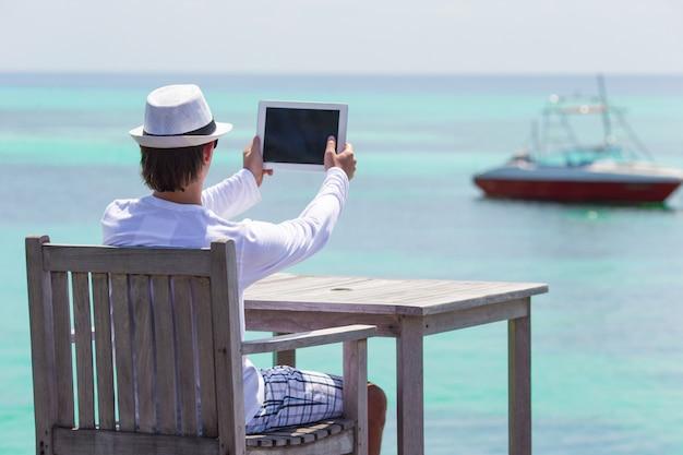 Joven hacer una foto en tableta en playa tropical
