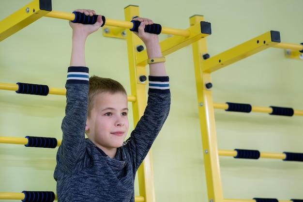Joven haciendo ejercicio en una barra de escalera de pared dentro del gimnasio deportivo