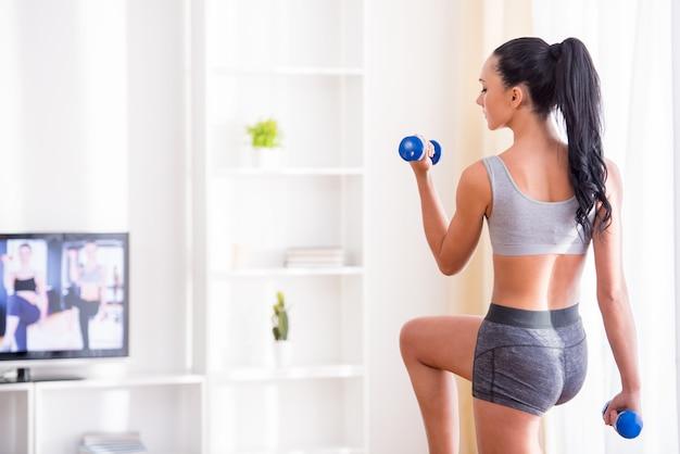 Joven está haciendo ejercicio con pesas en casa.