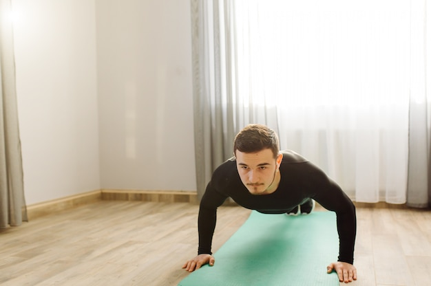 Joven haciendo ejercicios deportivos en casa
