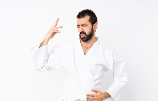 Joven haciendo karate sobre aislado con expresión cansada y enferma