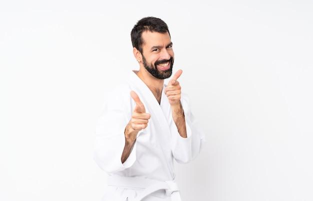 Joven haciendo karate sobre blanco aislado apuntando hacia el frente y sonriendo