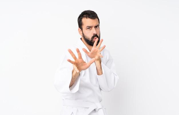 Joven haciendo karate sobre blanco aislado nervioso estirando las manos al frente