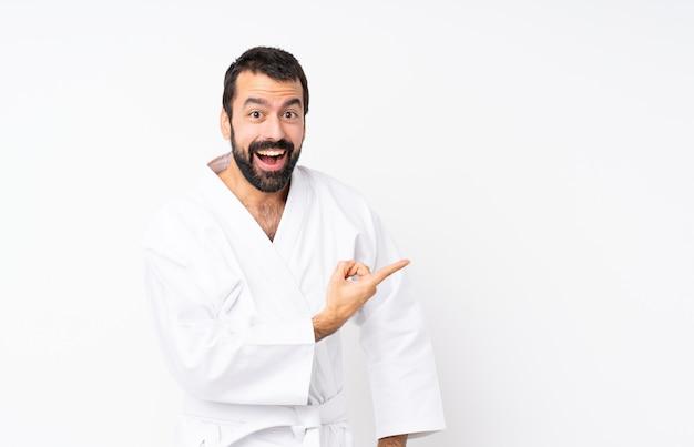 Joven haciendo karate sobre blanco aislado sorprendido y apuntando hacia el lado