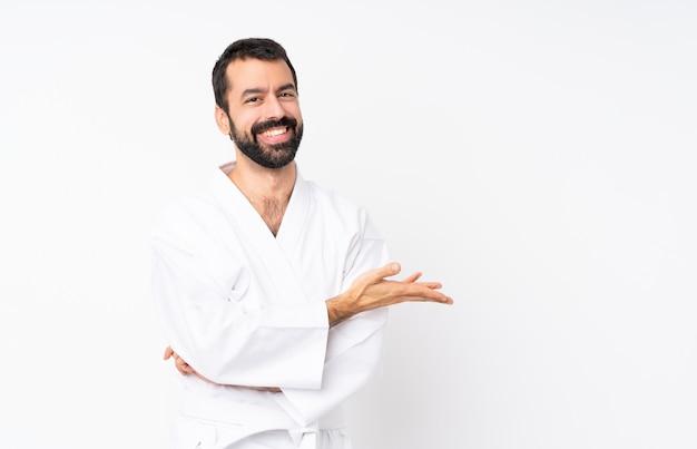Joven haciendo karate sobre blanco presentando una idea mientras mira sonriente hacia