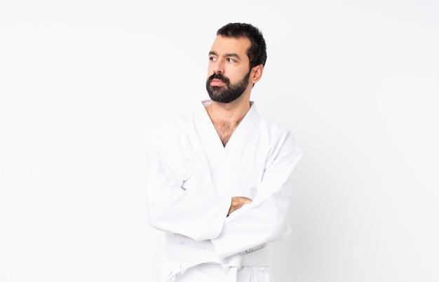 Joven haciendo karate sobre retrato blanco aislado