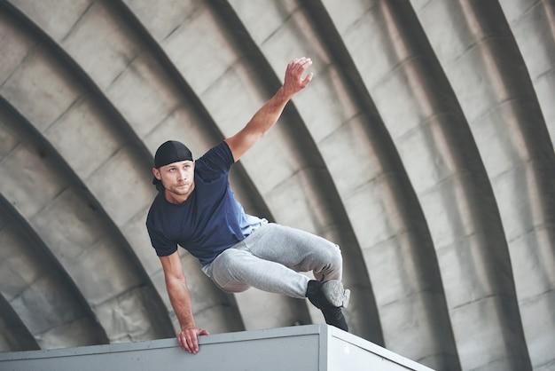 Joven haciendo parkour salto en el espacio urbano en la ciudad soleada primavera verano día.