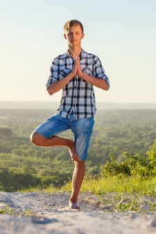 Joven haciendo yoga al aire libre en el concepto de salud sol