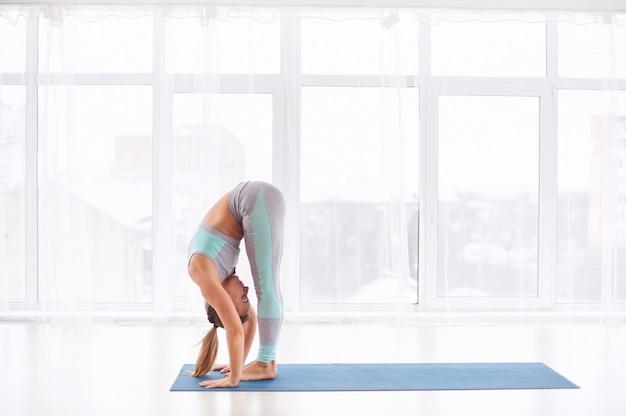 Joven está haciendo yoga asana uttanasana