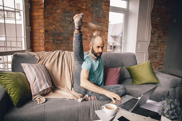 Joven haciendo yoga en casa mientras está en cuarentena y trabaja como autónomo en línea