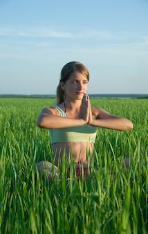 Joven haciendo yoga contra la naturaleza