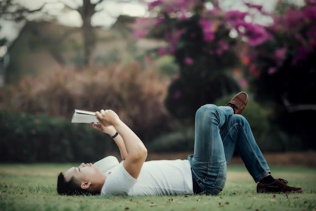 Joven hansome hombre leyendo libro