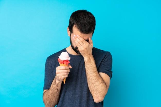 Joven con un helado de cucurucho sobre pared azul aislado con expresión cansada y enferma