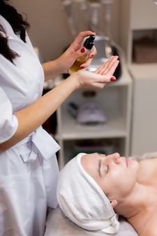 Una joven hermosa se acuesta en la mesa de la esteticista y recibe procedimientos, un ligero masaje facial.