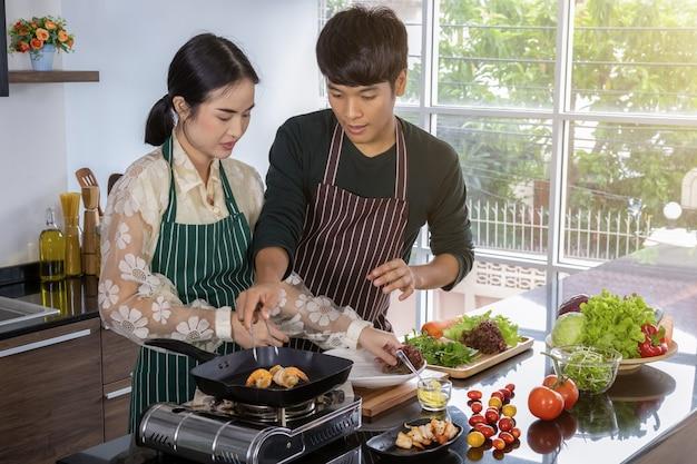 Un joven y una hermosa adolescente asiática están felices de hacer ensalada de camarones en una cocina moderna.