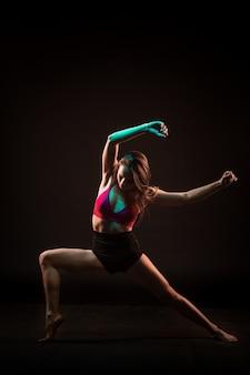 Joven hermosa bailarina bailando en la pared negra